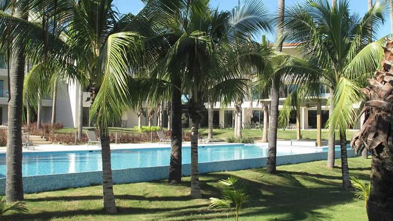 Alberca entre palmeras Condominio Península Golf en Nuevo Vallarta